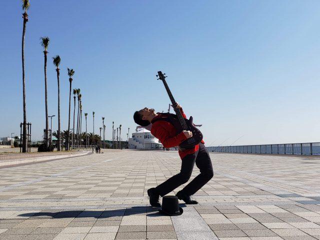 快晴の空の下でベースを弾く水野嘉彦氏